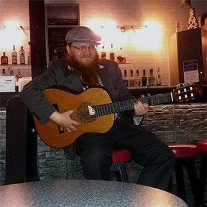 Dolfy playing the guitar at Pikari, pub.